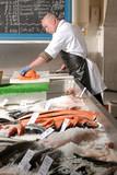fishmonger in fish shop wearing black apron poster