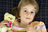 A young girl ill in bed with her teddy