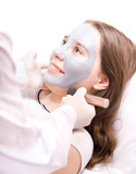Beautician applying a clay mask on face young woman poster