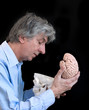 Mature man looking in an empty skull with brain in his hand.