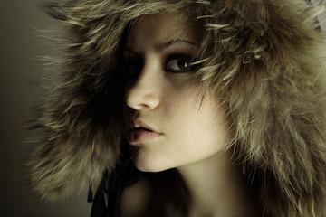 young elegant girl with fur coat. Studio portrait