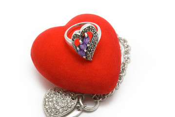 The silver ring with violet stones lays on red velvet heart.