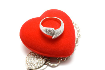 The silver ring lays on red velvet heart
