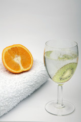 wine glass of water with kiwi, orange and towel