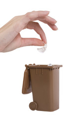 hand putting trash in recycling bin