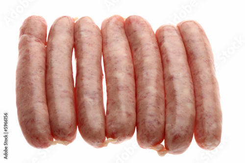 seven raw chipolata sausages on a white background