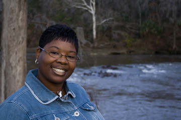 African American woman standing in front of a river