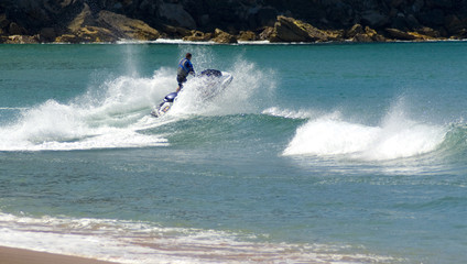 jetskier jumps jetski wave beach sending spray foam in air