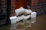 Sandbag barrier in doorway of flooded street in York. poster