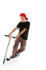 Child manoeuvring a scooter on a white backdrop
