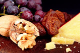 A board with walnuts, red grapes, figs, and sharp cheese. poster