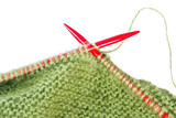 Knitting with green fluffy wool, on red knitting needles.  poster