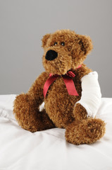 a teddy bear with a fractured arm at the hospital