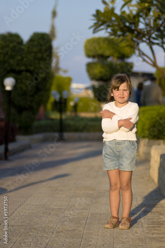 Little girl frozen of strong wind standing in sunset lights