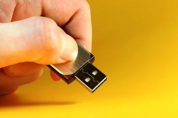 Hand zeigt einen USB-Stick in die Kamera
