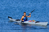 Athletic man is kayaking in calm blue waters of Mission Bay poster