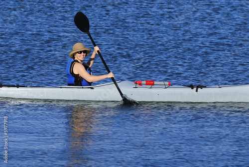 Cute young woman in straw hat is kayaking in idyllic blue waters