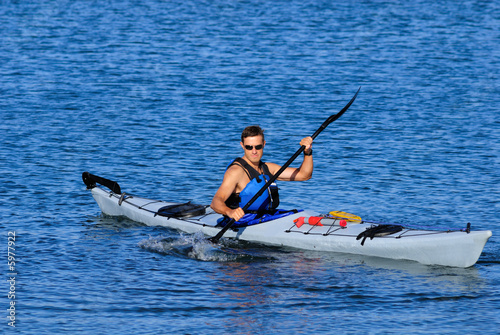 Athletic man is kayaking in calm blue waters of Mission Bay