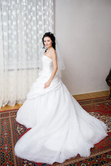a beatiful bride in a long white dress by the window