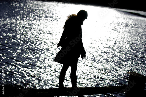 Silhouette of attractive woman at lake