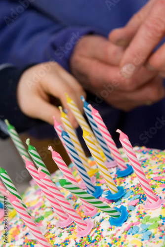 birthday cake with candles - old and young hands in background