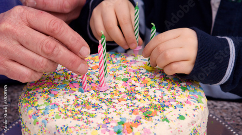 old & young hands place candles on a cake