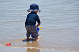 a little boy at beach with bucket and spade poster