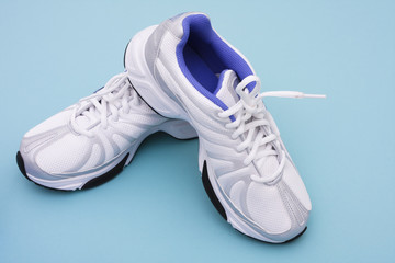Running shoes on blue background with copy space