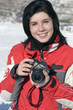 Attractive woman in sport wear holding a camera, winter outdoors
