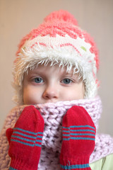 An image of a nice girl in a cap and red mittens