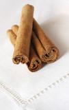 Cinnamon sticks on a beige linen napkin.  Shallow focus. poster