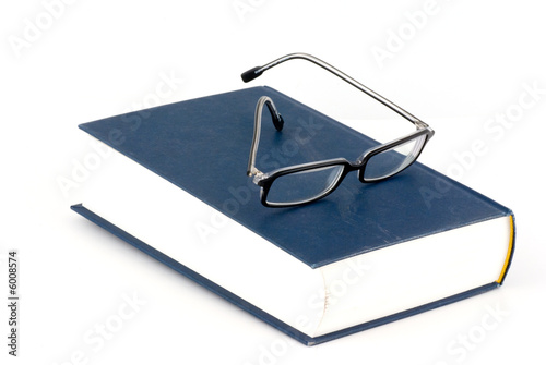 a book and a pair of glasses isolated on white