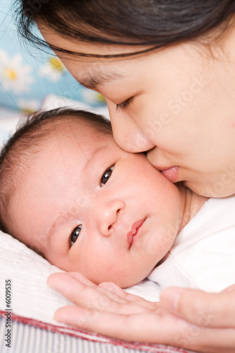 An asian mother kissing her baby boy