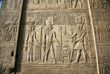 relief on a egyptian wall with a god a pharaoh an his wife poster