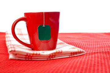 Red cup with tea-bag, over the red tablecloth. Shallow DOF