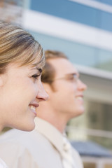profile of two businesspeople side by side smiling