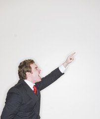 businessman in suit raising arm pointing and mouth open