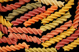 Different flavors of rotini twists pasta. Black background. poster