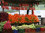 An outdoor stand selling many color vegetables. poster