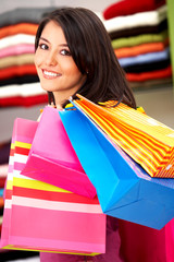 girl in a retail store smiling and carrying shopping bags