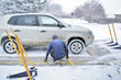 Man servicing car tires in the snow