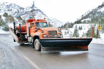 Snowplow on wet mountain highway