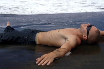 jeune homme allongé sur la plage