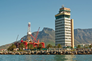 oil- rig in the bay near tower buildings and mountains