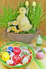 Basket full of easter decorations  - easter eggs and duckling