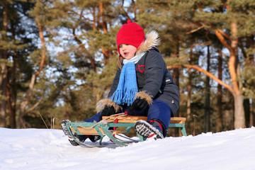 Girl sledding in sunny winter day