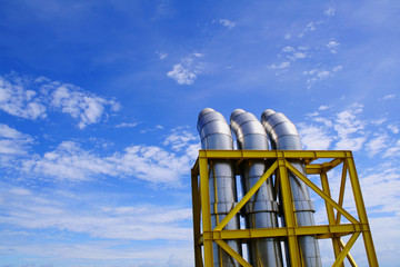 Exhausts under a blue sky with some clouds