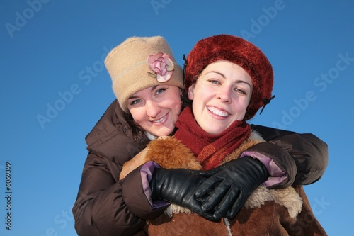 young woman embraces other against blue sky in winter