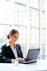 Portrait of business woman sitting at the table and typing