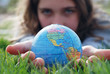 earth is being held by a little girl's hands